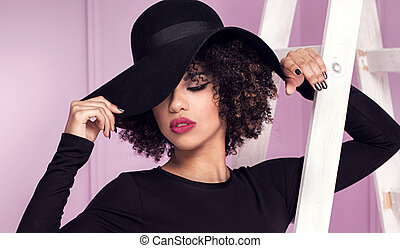 Fashionable girl in black hat posing. - Fashionable young...