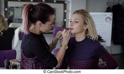 The master in a make-up prepares model for display in beauty...