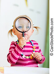 Toddler girl playing with magnifier - Portrait of adorable...