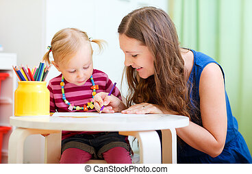 Mother and daughter drawing together - Young mother and her...