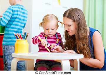 Mother drawing together with her daughter - Young mother and...