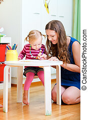 Mother and daughter drawing together - Vertical photo of...