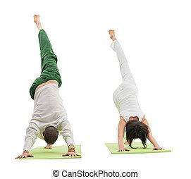 Couple doing yoga exercise in studio isolated shot - Couple...