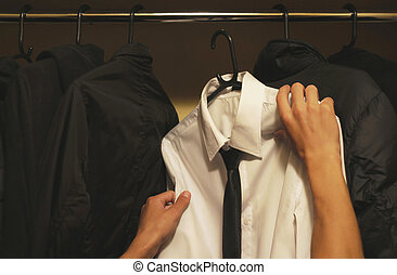 Chooses a white shirt in the wardrobe