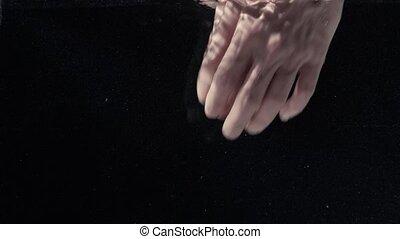 Man's hands under water on black background,
