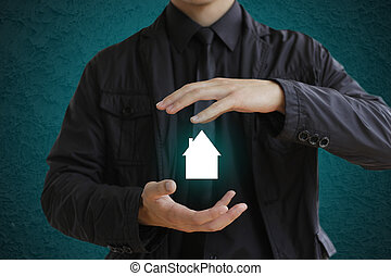 Businessman holding house sign