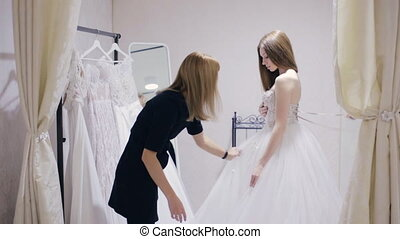 Pretty woman trying on wedding dress in fitting room - girl...