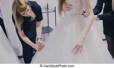 Pretty girl trying on wedding dress in fitting room - girl...