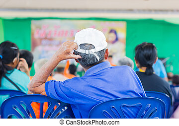 old man with white cap sitting back to camera
