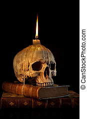 Candle on skull 1 - Halloween image with a burning candle on...
