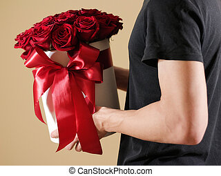 Man in black t shirt holding in hand rich gift bouquet of 21 red roses. Composition of flowers in a white hatbox. Tied with wide red ribbon and bow.