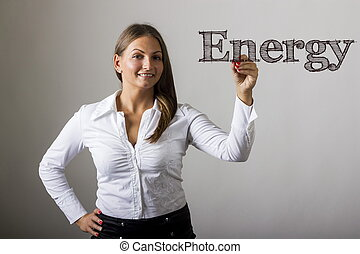 Energy - Beautiful girl writing on transparent surface -...
