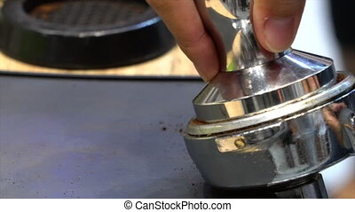 Barista tamping fresh ground coffee.