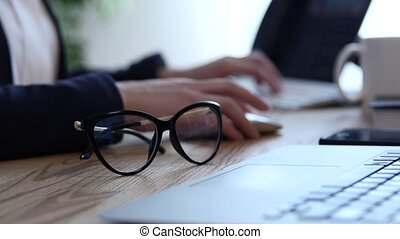 Office scene with notes and papers, a pen and pair of glasses. A young woman's hands are working on the laptop and taking notes in a notebook