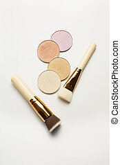 Set of highlighters with cosmetic brushes over a white background