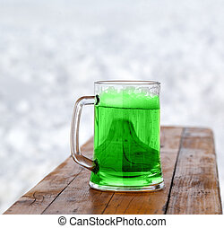 Full fresh cold glass of green beer on wooden bench - St....