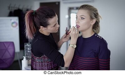 Experienced make-up artist very quickly paint the girl lips with the help of high-quality cosmetic pencil. Professional in the process of favorite work in a beauty salon. Leisure of beautiful women.