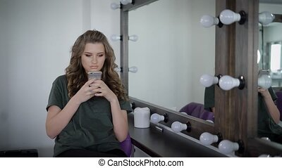 Heavily made girl with full lips sitting near mirror with...