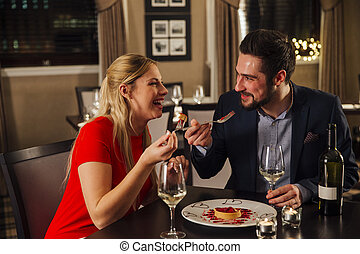 Valentine's Day Meal - Couple are sharing a dessert in a...