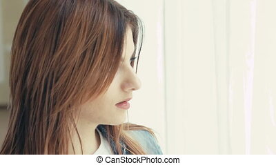 Portrait of pretty girl looking to camera on window background. Slowly