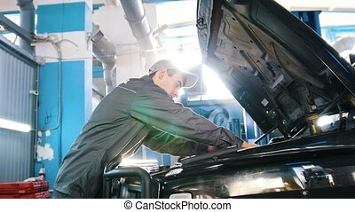 Mechanic in car service - repairing in engine compartment -...