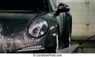 Washing a luxury car in the suds - telephoto, close up
