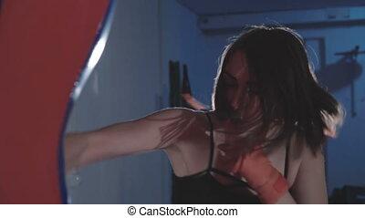 Pretty kickboxing woman training punching bag in sport...
