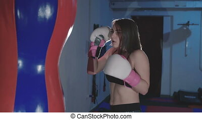 Pretty kickboxing woman training punching bag in sport...