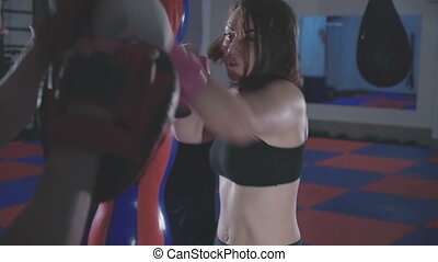 Pretty girl with trainer exercising kickboxing in gym
