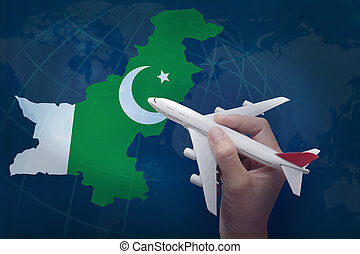 hand holding airplane with map of Pakistan.