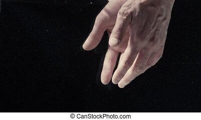 Man's hands under water on black background