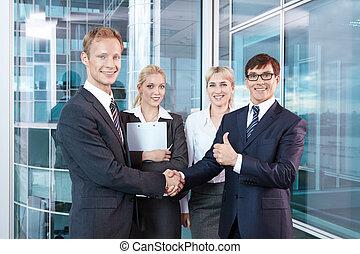 Negotiations - Businessmen shake hands after concluding a...