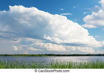 Landscape with river and cloudy sky. Sunny summer scene