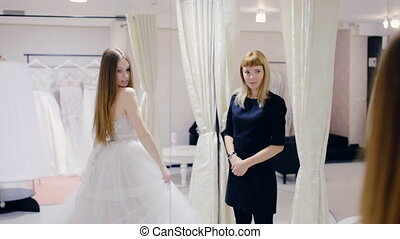 Pretty woman trying on wedding dress in fitting room -...