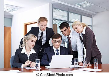 Staff - Serious people in business suits looking at laptop...
