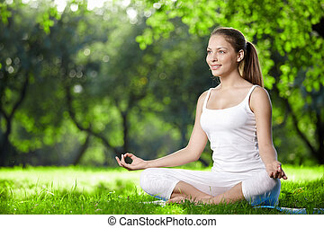 Meditation - Woman in lotus pose in the park