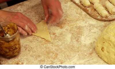Woman working with dough. making homemade croissants, cut...