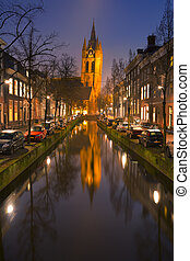 Church reflected in a canal in Delft, The Netherlands - The...