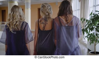 Three self-confident girls go directly to the office. Each of these elegant clothes by fashion designer, color stylish hairstyle. The back of one of the girls decorated with leopard tattoo