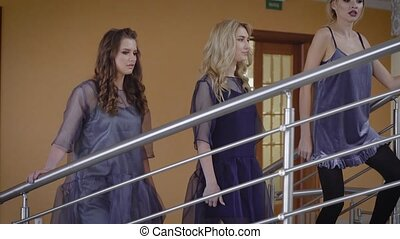 Professional models climb up the stairs in an expensive hotel after a successful photo session and fashion show. Luxury chicks talk and exchange glances with each other while walking.