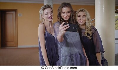 Foyer of the beautiful hall. Three girlfriends are very beautiful. The company of girls are ready to a magnificent party. Before an exit two fair-haired and the brunette take a selfie