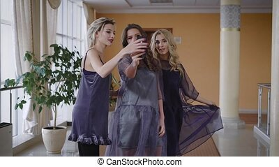 Happy chic female friends are celebrating party together and trying to make selfie. One of the girls is taking smartphone and inviting her colleagues to follow her to another place for shooting.