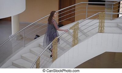 Spruced girl with hair iron is wound on up the marble stairs. Beauty wearing a designer dress made of synthetic fabric, it looks like a witness at the wedding or Birthday Girl
