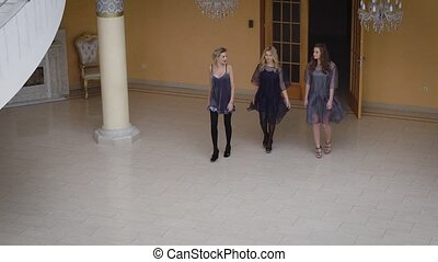 Hot young women showy gait walked through the luxurious hall...