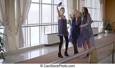 Three happy female friends posing for making selfie. Girls...
