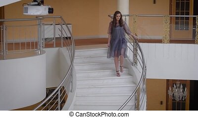 Photomodel walking down the white steps during backstage of professional photography. Long-haired girl in blue dress going downstairs in rich hall looking at the camera and posing for the picture.