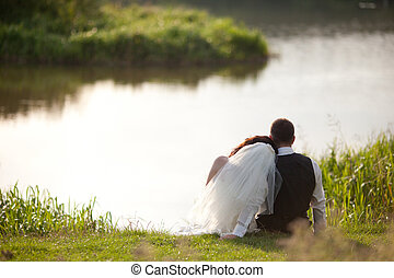 Just married couple rests on the lake shore  looking at the water