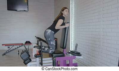 Girl athlete is engaged in the gym, in the fitness room....