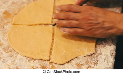 Woman cutting dough with a knife for that would prepare...
