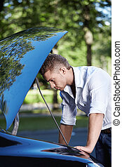 Auto Repair - Young attractive man looking under the hood of...
